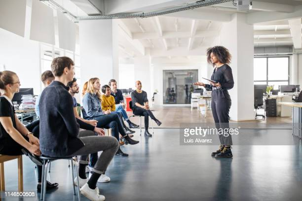 woman addressing her team - seminario riunione foto e immagini stock