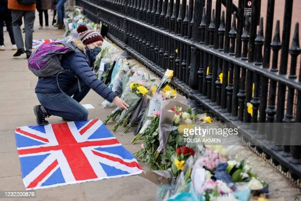 Woman adds a bunch of flowers to the tributes laid at the railings at the front of Buckingham Palace in central London on April 9, 2021 after the...