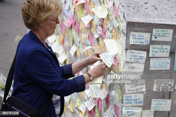 A woman adds a message of solidarity written on postit notes to a wall at the southern end of London Bridge in London on June 8 2017 following the...