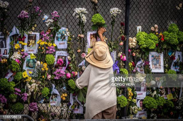 Woman adds flowers to a memorial featuring photos of some of those lost in the partially collapsed 12-story Champlain Towers South building on June...