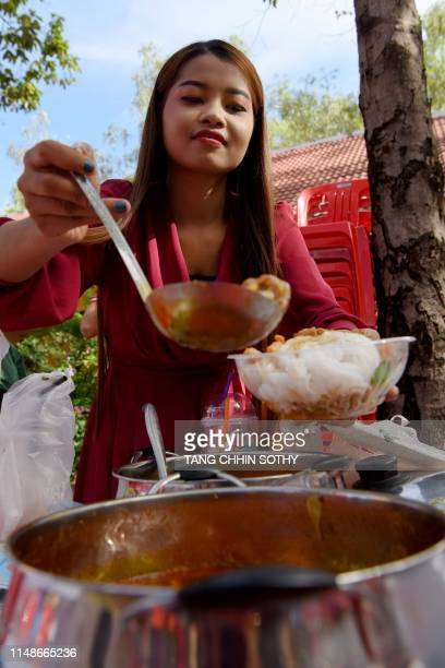 A woman adds soup to her bowl of noodles during a noodles feast at a pagoda in Phnom Penh on June 9 2019 Cambodia's Prime Minister Hun Sen urged his...