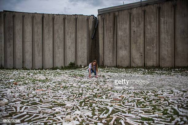 A woman adjustes ceramic bones as part of 'The One Million Bones' project in front of the hall at the Potocari cemetery and memorial near Srebrenica...
