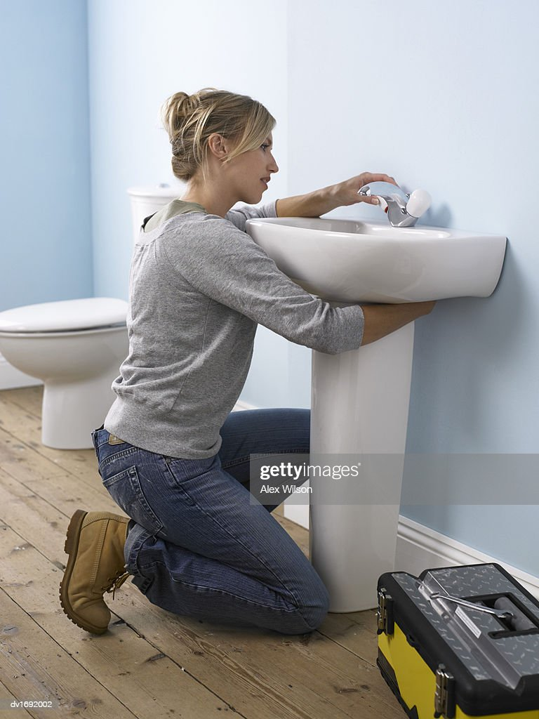 Woman Adjusting a Faucet in a Domestic Bathroom : Stock Photo