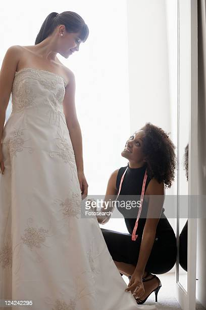 woman adjusting bride's wedding dress - length stock pictures, royalty-free photos & images