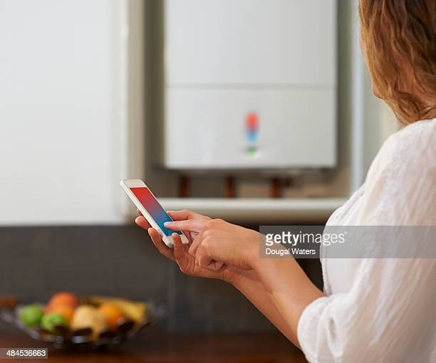 Woman adjusting central heating with smart phone.