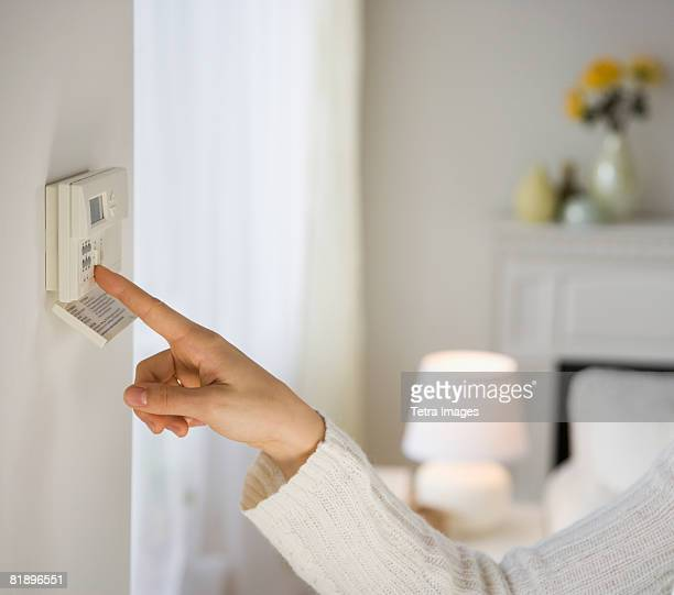 Woman adjusting digital thermostat