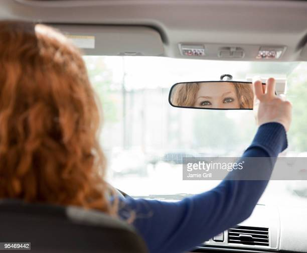 Woman adjusting driving mirror