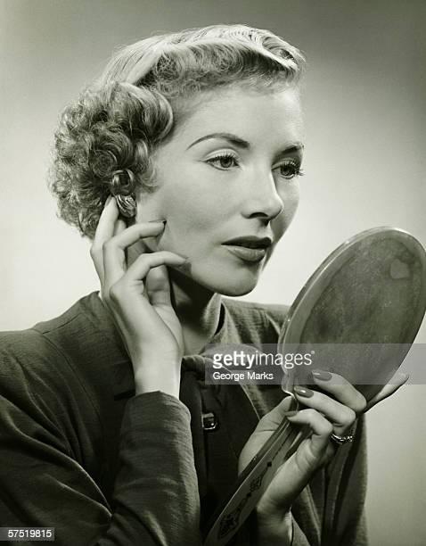 Femme ajuster d'oreille, tenant un miroir à main (B & W), portrait