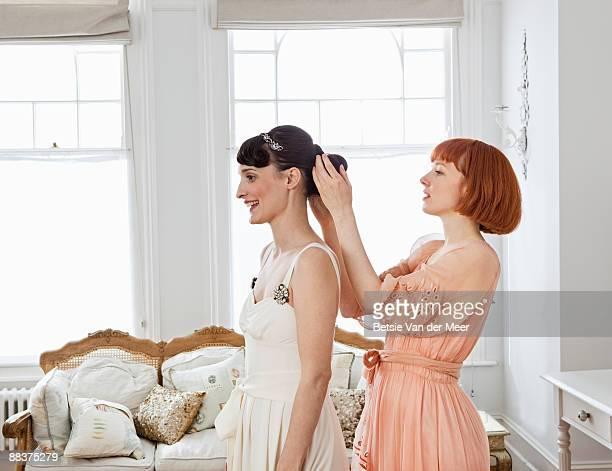Woman adjusting hair of bride.