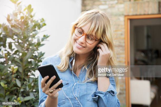 Woman adjusting headphone while listening to music standing in garden.