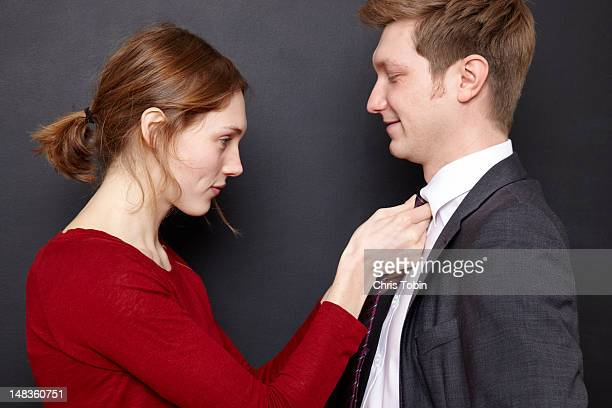 woman adjusting her husband's tie - adjusting necktie stock pictures, royalty-free photos & images