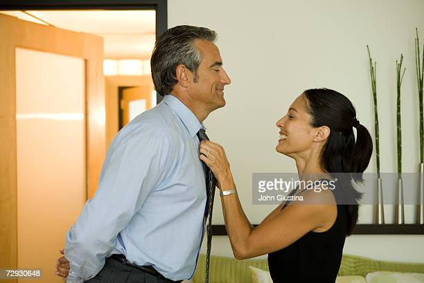 Woman adjusting husband's tie at home
