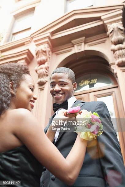 Woman adjusting man's boutonniere