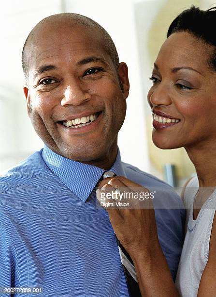 Woman adjusting man's tie, smiling, close-up