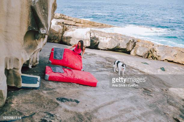 Woman Adjusting Mattress By Rock Formation At Beach