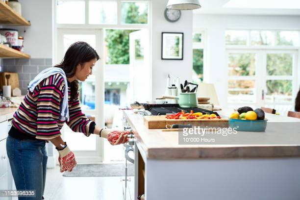 woman adjusting oven and preparing dinner in kitchen - pretty vietnamese women stock pictures, royalty-free photos & images