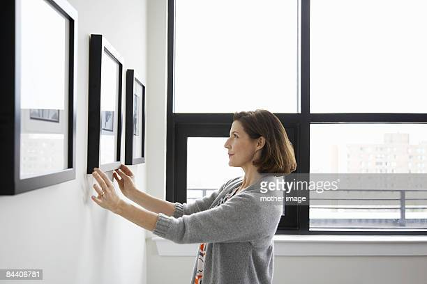 woman adjusting picture frame at home - perfection stock pictures, royalty-free photos & images