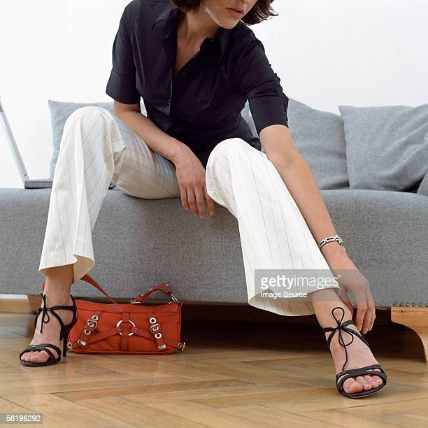 woman adjusting sandal - women trying on shoes stock pictures, royalty-free photos & images