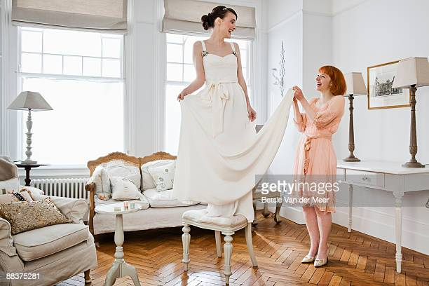 woman adjusting seam of brides dress. - bride stock pictures, royalty-free photos & images