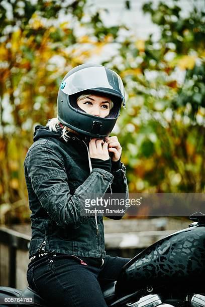 Woman adjusting strap on helmet before ride