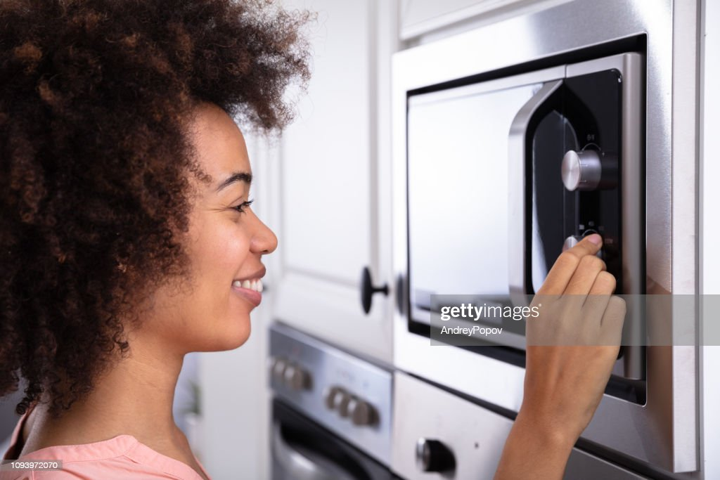 Woman Adjusting Temperature Of Microwave Oven : Stock Photo