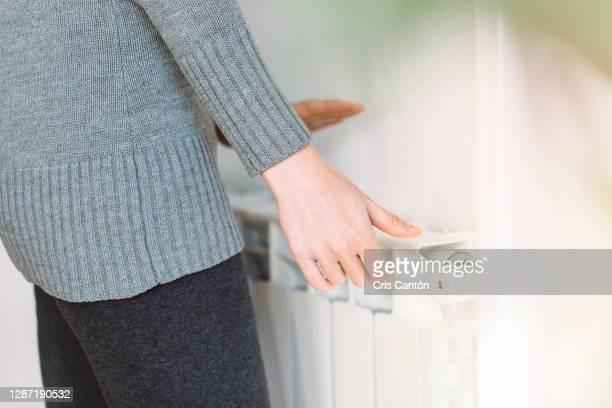 woman adjusting temperature on radiator - cris cantón photography fotografías e imágenes de stock