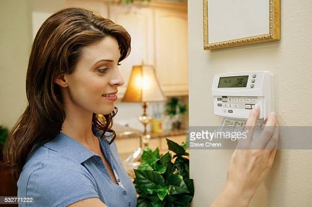 woman adjusting thermostat at home - エアコン ストックフォトと画像