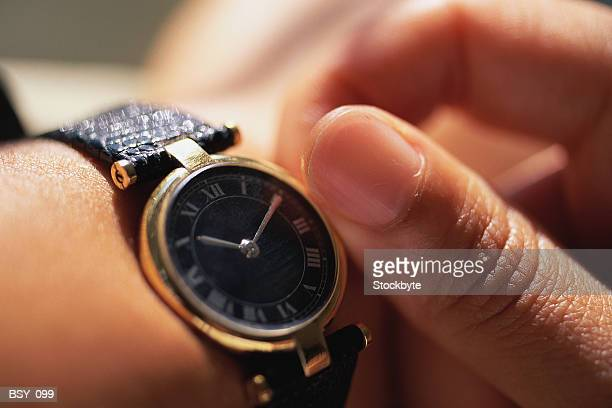 Woman adjusting watch  close-up