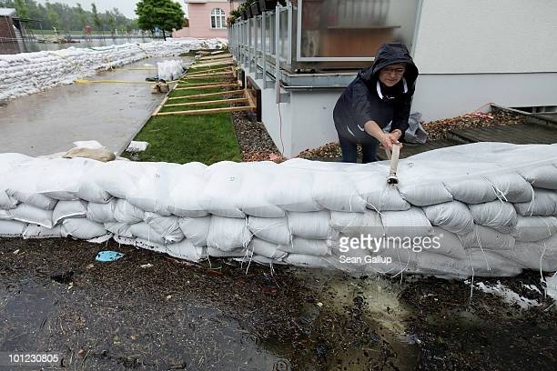 A woman adjusts a hose spewing floodwater pumped from a nearby house's basement behind sandbags on a flooded street on May 28 2010 in...