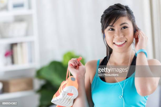 Woman adjusts earbuds before her morning run