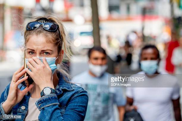 Woman adjusts her face mask on the street during the coronavirus crisis. The wearing of a face mask will become compulsory from Saturday in shops and...