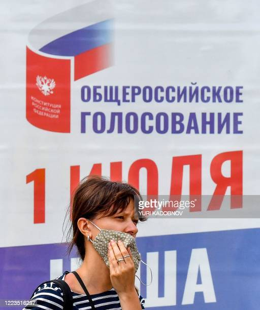 Woman adjusts her face mask standing in front of a poster informing of a national vote on constitutional changes in Moscow on June 30, 2020. -...