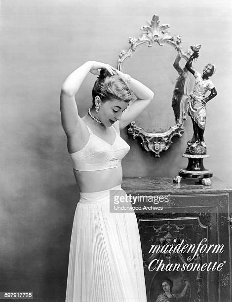Woman adjusts her hair as she poses in an ad wearing her Maidenform Chansonette bra, 1949.