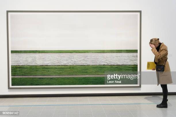 A woman adjusts her hair before posing in front of Rhine II by Andreas Gursky in the reopened Hayward Gallery on January 24 2018 in London England...