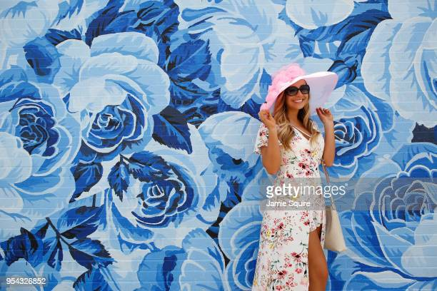 A woman adjusts her hat in front of a wall of painted roses ahead of the 144th Kentucky Derby at Churchill Downs on May 3 2018 in Louisville Kentucky