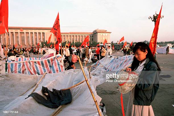 A woman adjusts her hat near makeshift tents in Tiananmen Square Prodemocracy demonstrators and protestors filled the square for weeks prior to the...