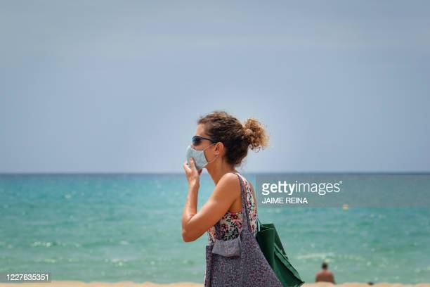 Woman adjusts her mask at Palma Beach in Palma de Mallorca, at Spain's Balearic island of Majorca on July 16, 2020. - Regional authorities on Spain's...