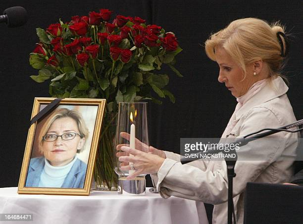 A woman adjusts the candle next to red roses and a portrait of late Swedish Foreign Minister Anna Lindh that decorate the black podium where Swedish...