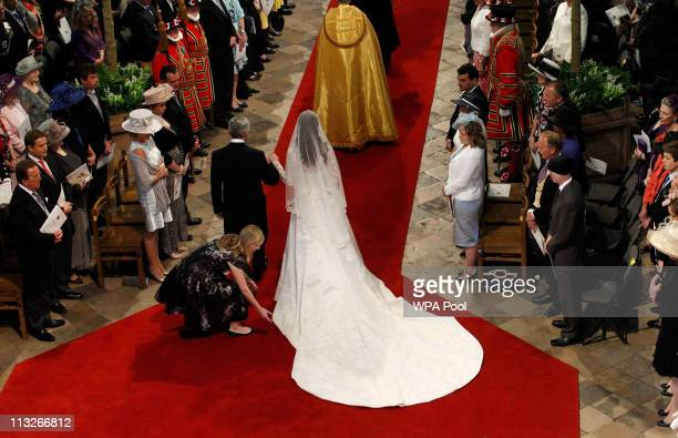 A woman adjusts the dress of Catherine Middleton as she arrives with her father Michael Middleton at Westminster Abbey on April 29 2011 in London...
