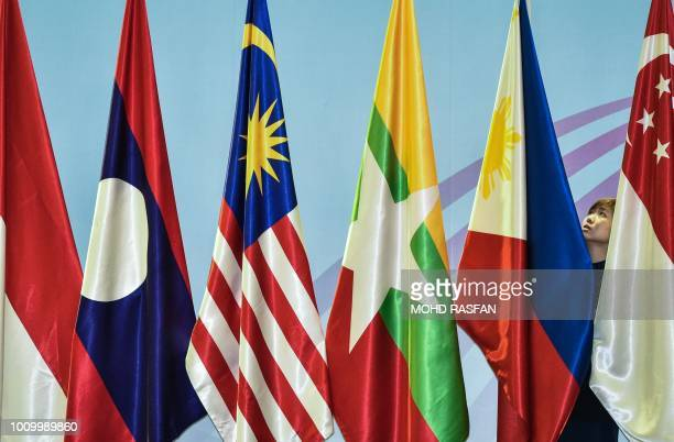 A woman adjusts the Philippines flag before the 51st Association of Southeast Asian Nations Republic of Korea Ministerial Meeting in Singapore on...
