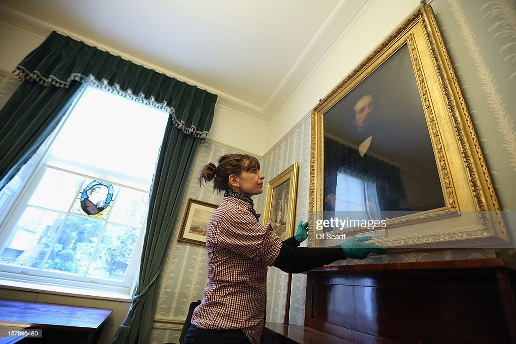 A woman adjusts the picture frames in the Morning Room inside the Charles Dickens Museum on December 7, 2012 in London, England. The museum will re-open to the public on December 10, 2012 following a major 3.1 million GBP refurbishment and expansion programme to celebrate Dickens' bicentenary year. The museum is located in Charles Dickens' house on Doughty Street where he lived from 1837 until 1839 and in which he wrote many novels including Oliver Twist and Nicholas Nickleby.