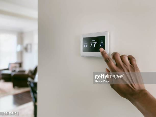 woman adjusts thermostat - heat stock pictures, royalty-free photos & images