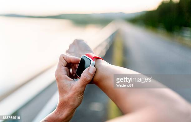 Woman adjustung settings of smart watch for outdoor training