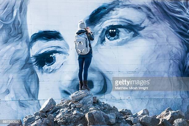 A woman admires a building mural.