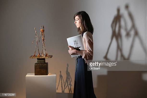 A woman admires a sculpture by ALberto Giacometti entitled 'Trois hommes qui marchent II' in Sotheby's auction house on June 17 2011 in London...