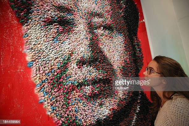 A woman admires an artwork by Joe Black of Mao Zedong entitled 'Workers of the World Unite' which is made from 9000 handpainted toy soldiers in the...