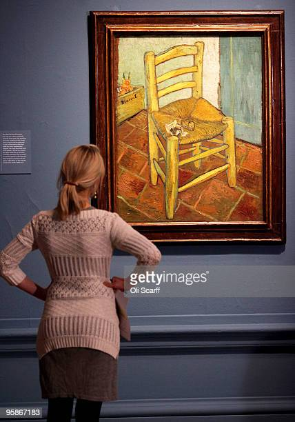 A woman admires an oil painting by acclaimed Dutch artist Vincent Van Gogh entitled 'Van Gogh's Chair' in an exhibition of his work held at the Royal...