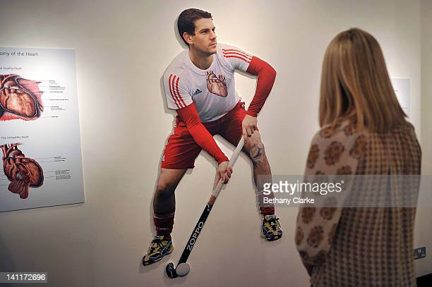A woman admires Hockey by Jo Culley on March 12 2012 in London England The image shows Elite Hocky Player Richard Smith with a diagram of his heart...