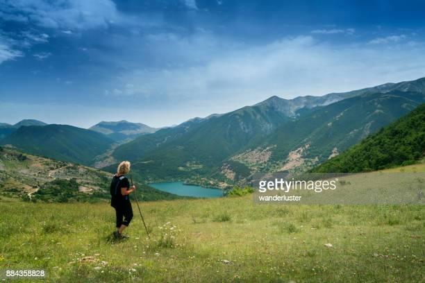 女性がイタリアの山中湖の景色を賞賛します。 - アブルッツォ州 ストックフォトと画像