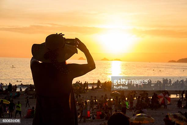 Woman admires the sunset at Ipanema beach Sunset on a sunny day in Rio de Janeiro Cariocas and tourists watch the sun set on the horizon this...